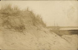 Sand dune with boat in background