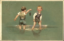 Two boys play in the water while one holds a mouse by the tail