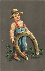 Boy with floppy hat is holding a large horseshoe