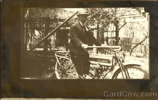 Man riding an early motorcycle Men