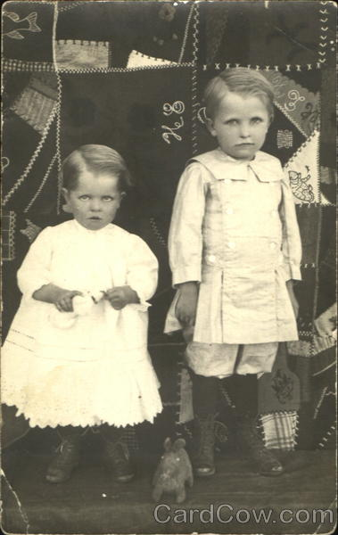 Two children posing in front of patchwork quilt