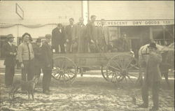 Men standing in a wagon in front of the dry goods store