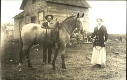 Couple with Horse in Front of House