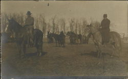 Men herding horses in corral