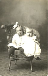 Two Young Children sitting in a Wicker Chair