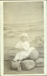 Portrait of Child with Seascape Behind, holding a Spade