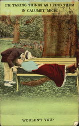 Man kissing woman in red skirt as she lies on a bench Postcard