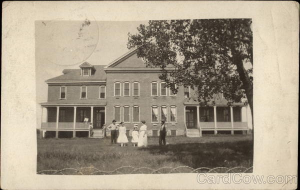 Old boarding house with people in front yard Buildings