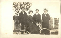 Woman on Bicycle with three people watching