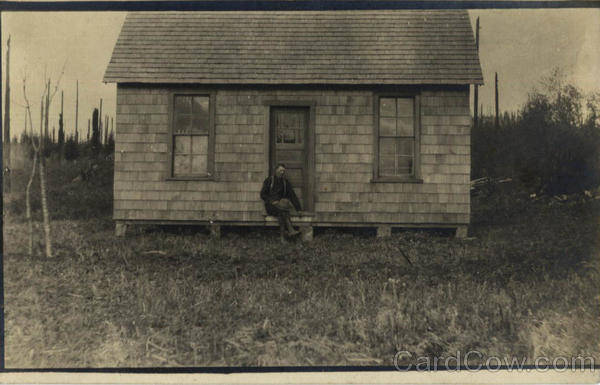 Man in front of Cottage Buildings