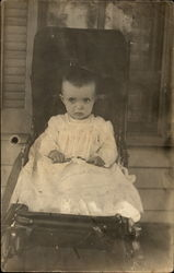 A Baby Sitting in a Chair Postcard
