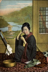 Japanese woman sites on a rug before a mirror