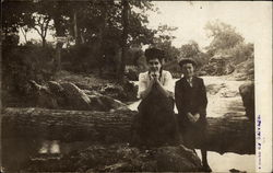 Woman and boy sitting on a log