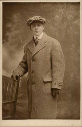 Young man in Overcoat and Cap with hand on chair