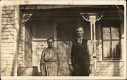 A Couple Pose on Front Porch of Clapboard House