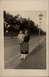 Woman Holding a Baby by a Streetlamp