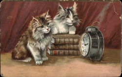 Two kittens looking at an alarm clock