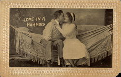 black and white photo of a couple sitting on a hammock and kissing Postcard