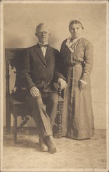 Photograph of Seated Man and Standing Woman