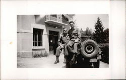 Two Soldiers Sitting on Army Jeep