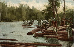 Men Move Felled Logs Along a River
