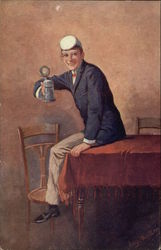 Young Man sitting on Table holding a Stein