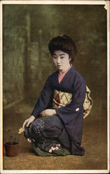 Geisha Girl Kneeling beside Flower Pot