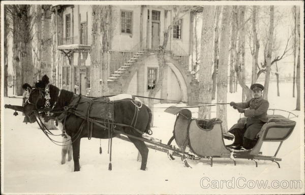 Horse-drawn sleigh in snow in front of mansion Horses