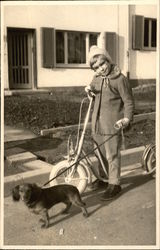 Little Girl with Scooter holding Dachshund on Leash