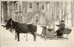 Horse-drawn sleigh in snow in front of mansion
