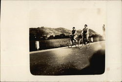 Two Women Riding Bicycles on Open Road