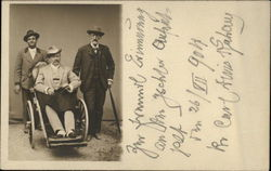 3 men in hats, one in wheelchair Postcard