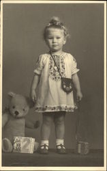 Very Young Girl in Embroidered Dress with Teddy Bear and Book
