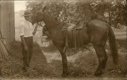 Man standing in Barnyard with Saddled Horse