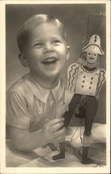 Young Blonde Boy Laughing with his Toy