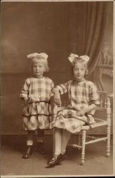 Two Young Girls in Check Dresses