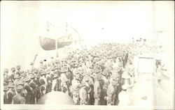 Crowd of men stand on a ship dock