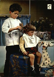 A picture of a boy pretending to be a haidresser and a girl pretending to be his customer Postcard