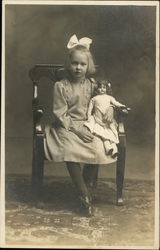 Little Girl with White Bow in Hair Holding Doll While Sitting in Chair