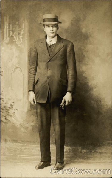 Man standing, in dark suit and hat Binghamton New York