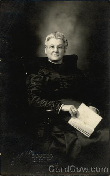 Woman dressed in black, sitting & holding a book Women