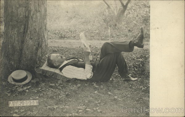 Man laying under a tree reading, Aug. 1911 Binghamton New York