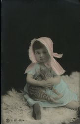 Girl in pink bonnet & blue dress holding cat