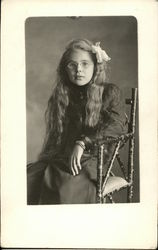 Girl with long hair and glasses sitting on chair