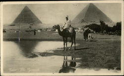 Sitting on a camel, pyramids in background