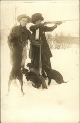 Man and woman with rifles, dogs at feet