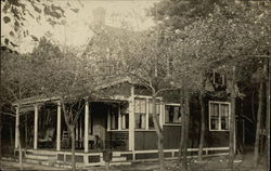 House with porch, surrounded by trees