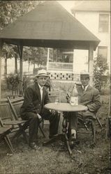 Two men sitting at round table outside