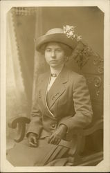 Woman, sitting, with gloves & flowered hat