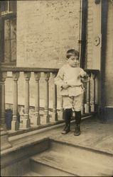 Young Boy Standing on Porch